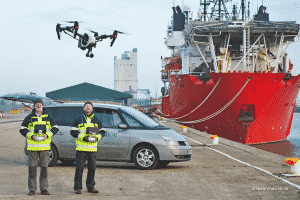 Two Men Flying Drone by Ship
