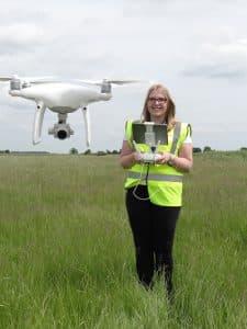 Woman Flying Drone in Field
