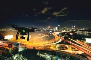 Drone Flying Above City at Night