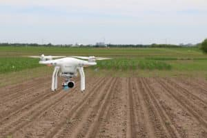 White Drone Flying Over Farmland