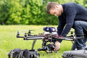 Man Adjusting Drone Camera Equipment