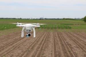 White Drone Flying Over Farmland